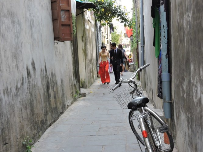 A couple is seen walking in a small alley in Hoi An Ancient Town. Photo: Tuoi Tre
