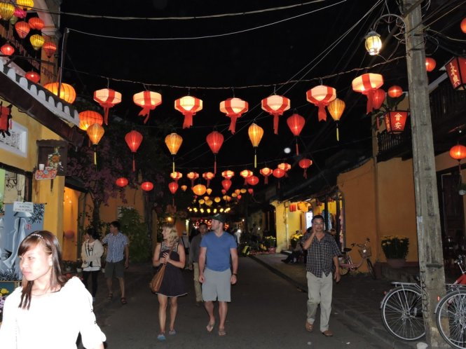 Foreigners are shown marvelling at Hoi An Ancient Town's charm in the dim light of colorful lanterns. Photo: Tuoi Tre